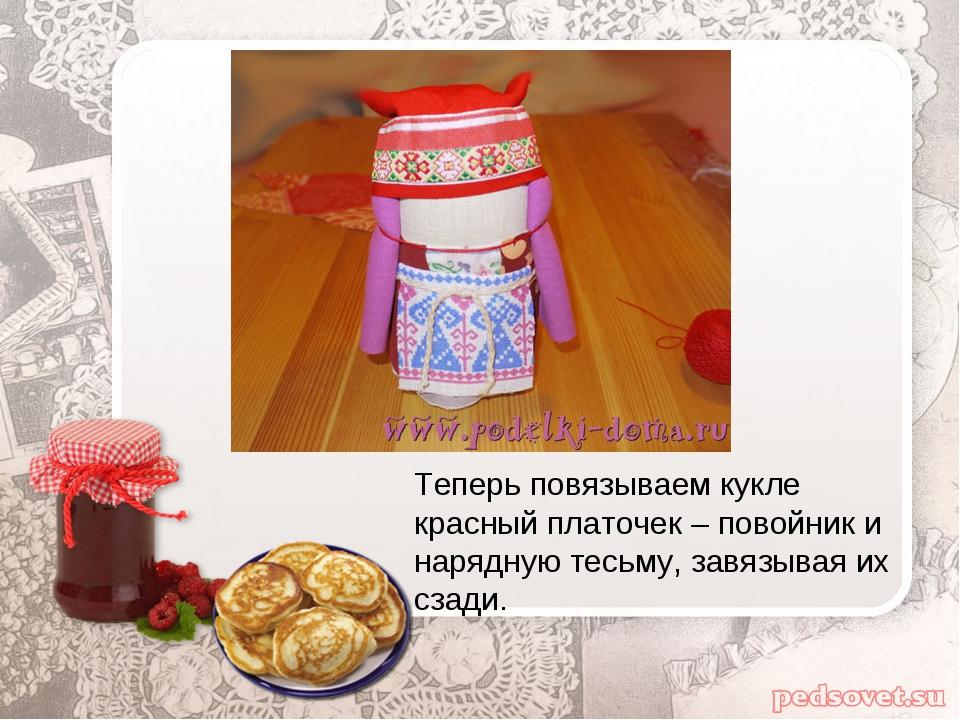 Теперь повязываем кукле красный платочек – повойник и нарядную тесьму, завязы...